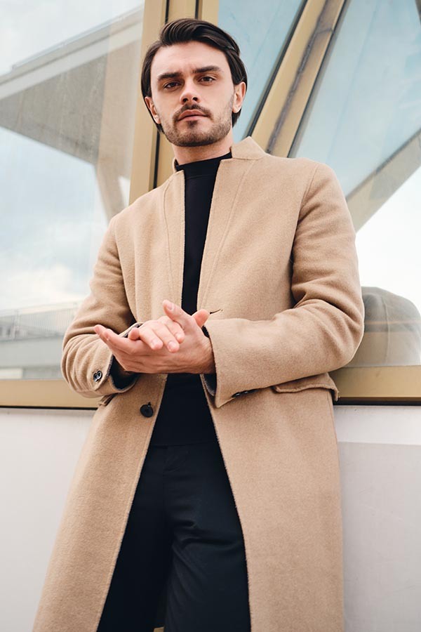 Young serious stylish man in beige coat confidently looking in camera outdoor