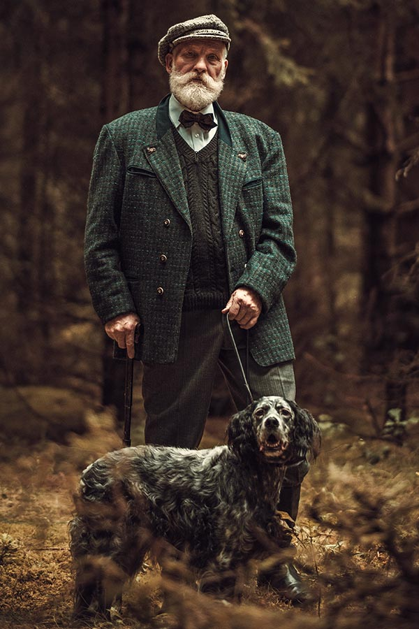 Senior man with dog in a traditional shooting clothing on a dark forest background.